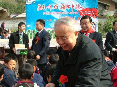图:工作委员会常务主任刘凡林给小学生送奶