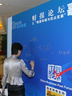 图文:主持人杨澜正在签到板上签字