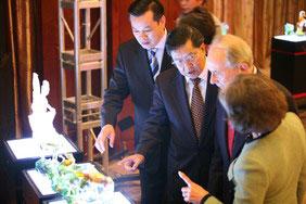 图文:贵宾们在欣赏千玉集团捐赠的精美琉璃拍品