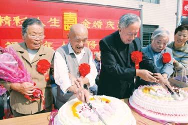 """胸前戴着大红花的老人在切""""金婚""""庆典大蛋糕"""