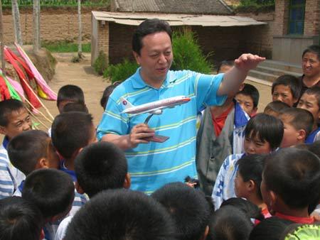 图文:谢建华向孩子们演示飞机起飞过程