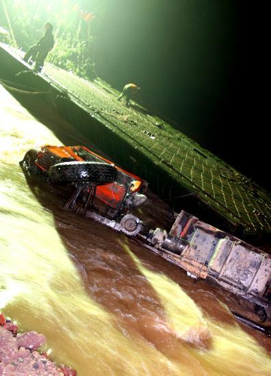 图文:一辆报废的卡车被推入河中封堵洪水