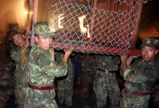 图文:官兵抬着填装沙袋用的铁笼投入堵口战斗
