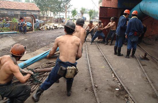 图文:抢险矿工在井口铺设排水管