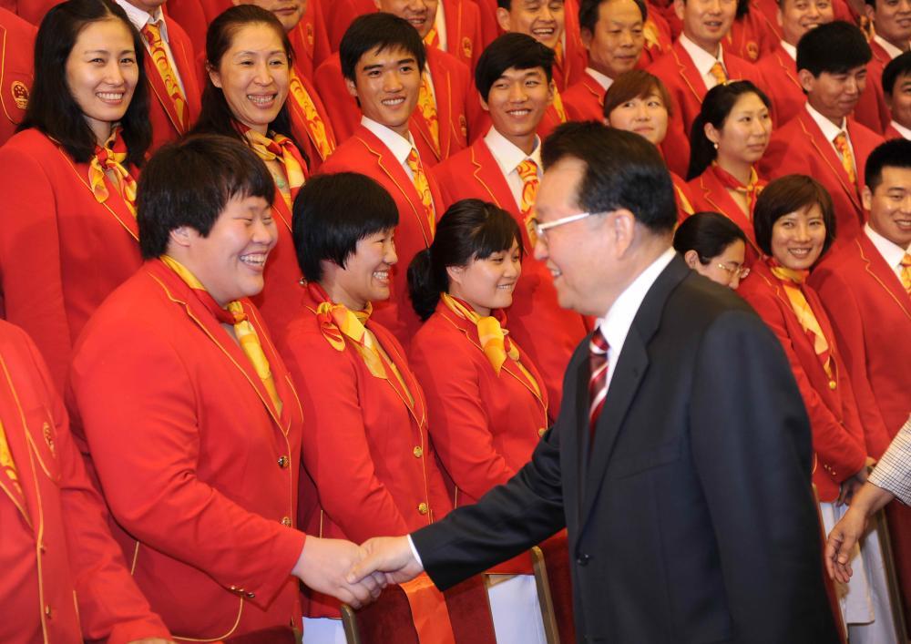 中共中央政治局常委李长春与柔道运动员佟文握手