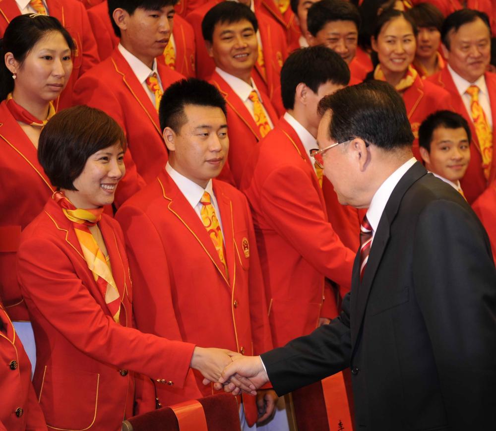 中共中央政治局常委李长春与射击运动员杜丽握手