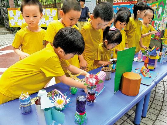 活动中,幼儿园的小班孩子和家长利用厕纸筒,一次性餐具,塑料瓶等