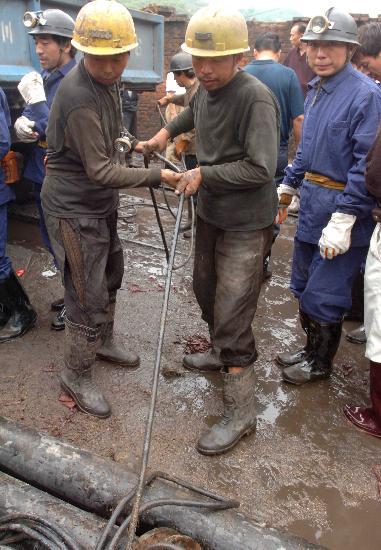 图文:抢险救援人员在井口拉缆绳