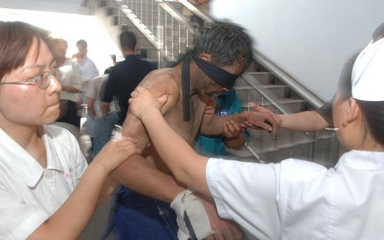 图文:医务人员搀扶一名被救矿工进入医院