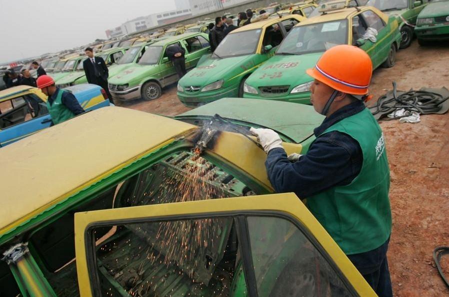 并套用有正规手续的出租车牌照.图为工人现场切割克隆出租车.3