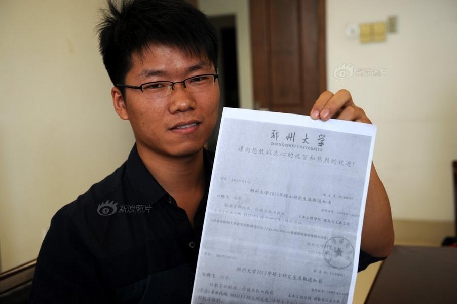 接受媒体群访,展示自己的录取通知书复印件.-郑州大学保安考上名