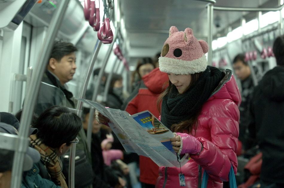 一位乘客在北京地铁亦庄线首班车上查看地铁地图.当日下午,北京图片