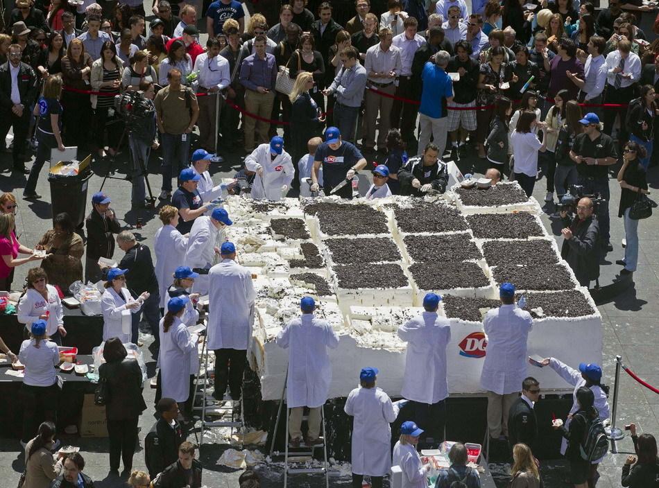 大多伦多市的邓达斯广场,工作人员将巨大的冰淇淋奶油蛋糕切成