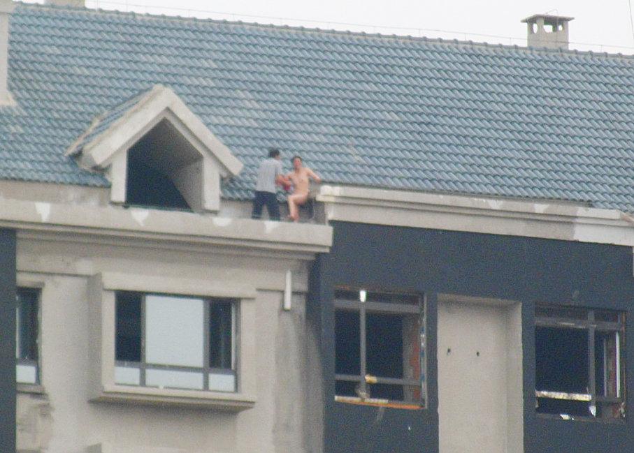 女贼脱衣全裸逃上楼顶对抗 社会