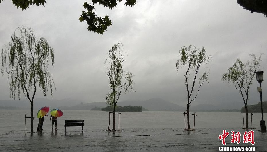 """10月7日,风雨中两名游客成为美化杭州西湖的色彩.强台风""""菲特"""""""