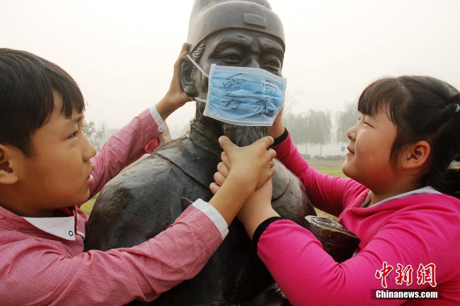 """10月10日,河北省广平县明德小学开展""""我给校内先贤雕像戴口罩""""活动,通过活动让更多人意识到,雾霾现在真的很严重,我们每个个体都需要加强环保意识,从自身做起,行动起来。"""