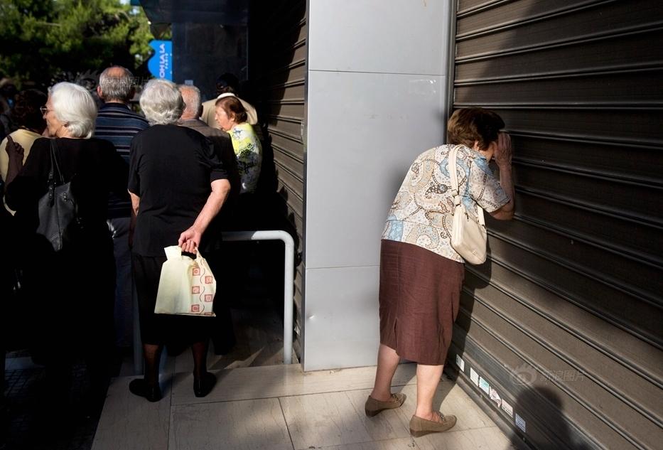 拄着拐杖的老人只能对着卷帘门望洋兴叹.-希腊银行关闭 老人门前