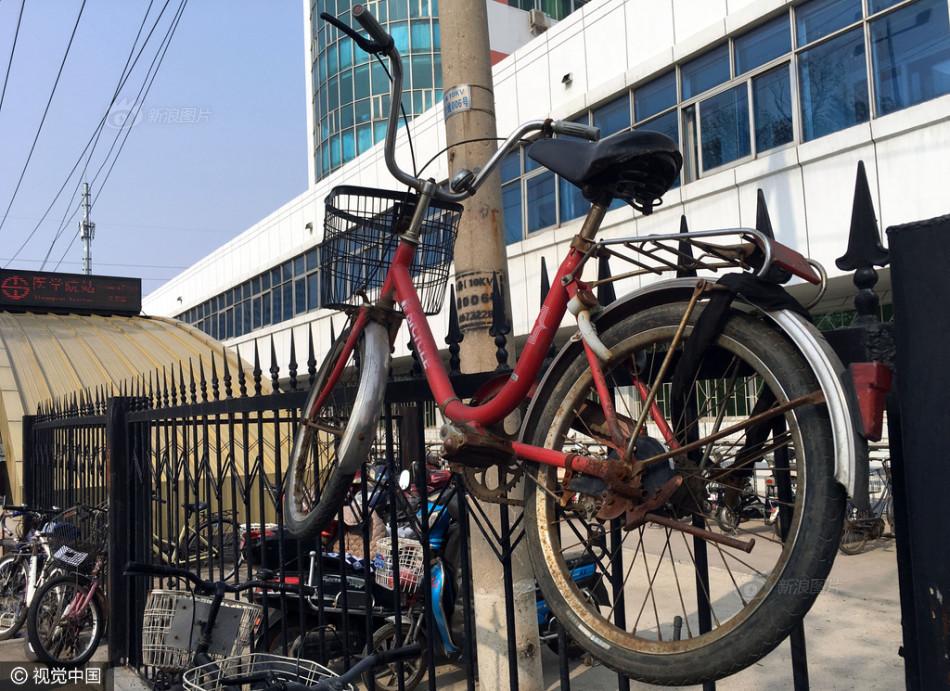 自行车难觅停车位 市民出奇招墙上锁车