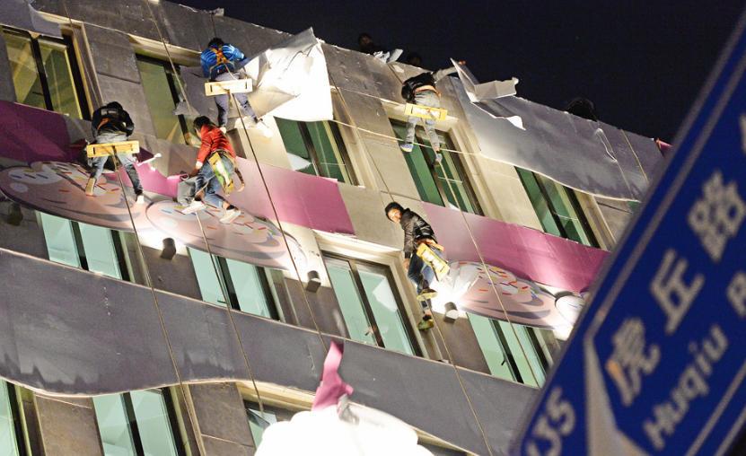 2016年11月2日,上海外滩,工人连夜拆除蛋糕楼外墙装饰。近日,上海外滩附近出现了一栋8层粉色蛋糕楼,有专家指出其破坏了外滩建筑群的整体风格,并质疑其违反了历史文化风貌区的保护的相关条例。 澎湃新闻见习记者 赖鑫琳 图