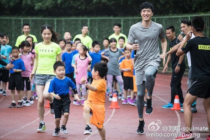 这块他熟悉的场地,在跑道上教孩子们做跑步前的热身运动.-刘翔和