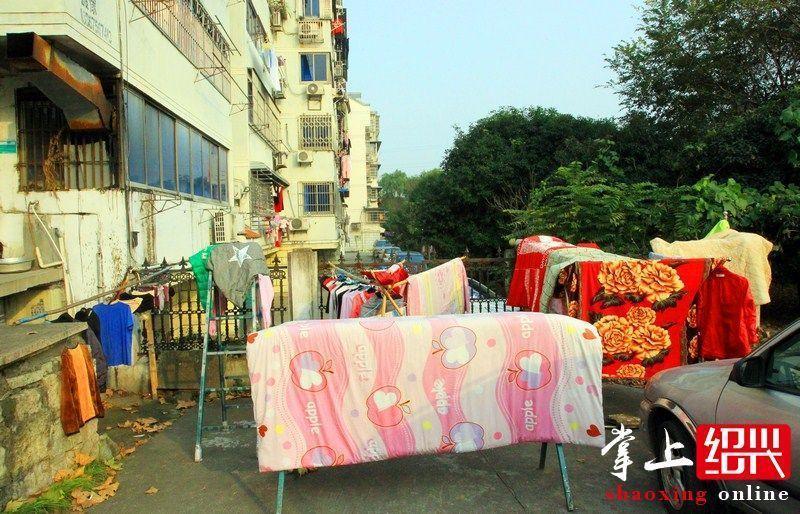 """了附近居民的""""晾衣杆"""",上面搭满了被子和衣物.这样晒被既不"""