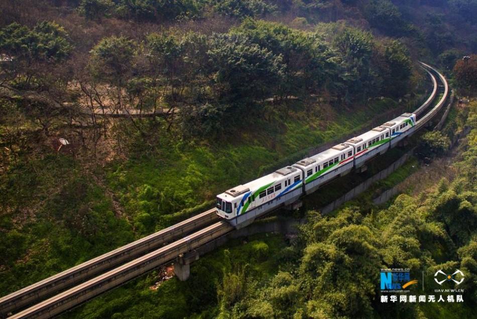 图为重庆轨道交通2号线列车如游龙一般穿梭于春意盎然的丛山之间