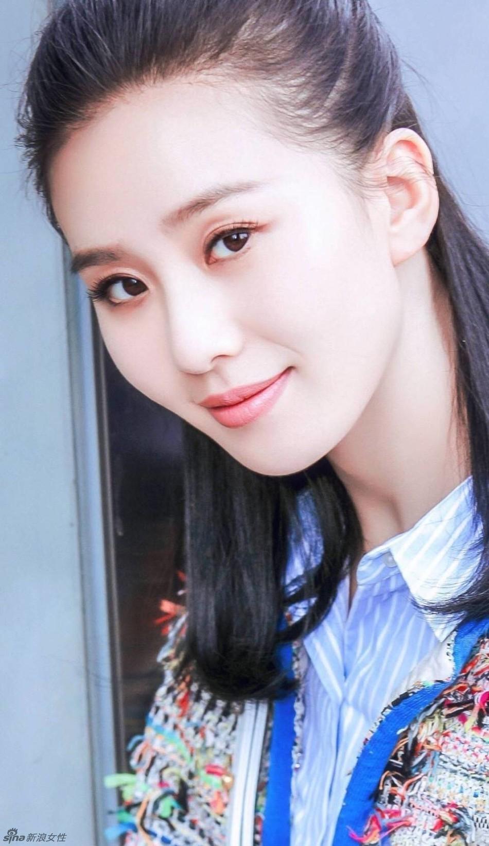 刘诗诗身穿流苏外套搭配蓝色条纹衬衫,扎起半丸子头温婉不失可爱.
