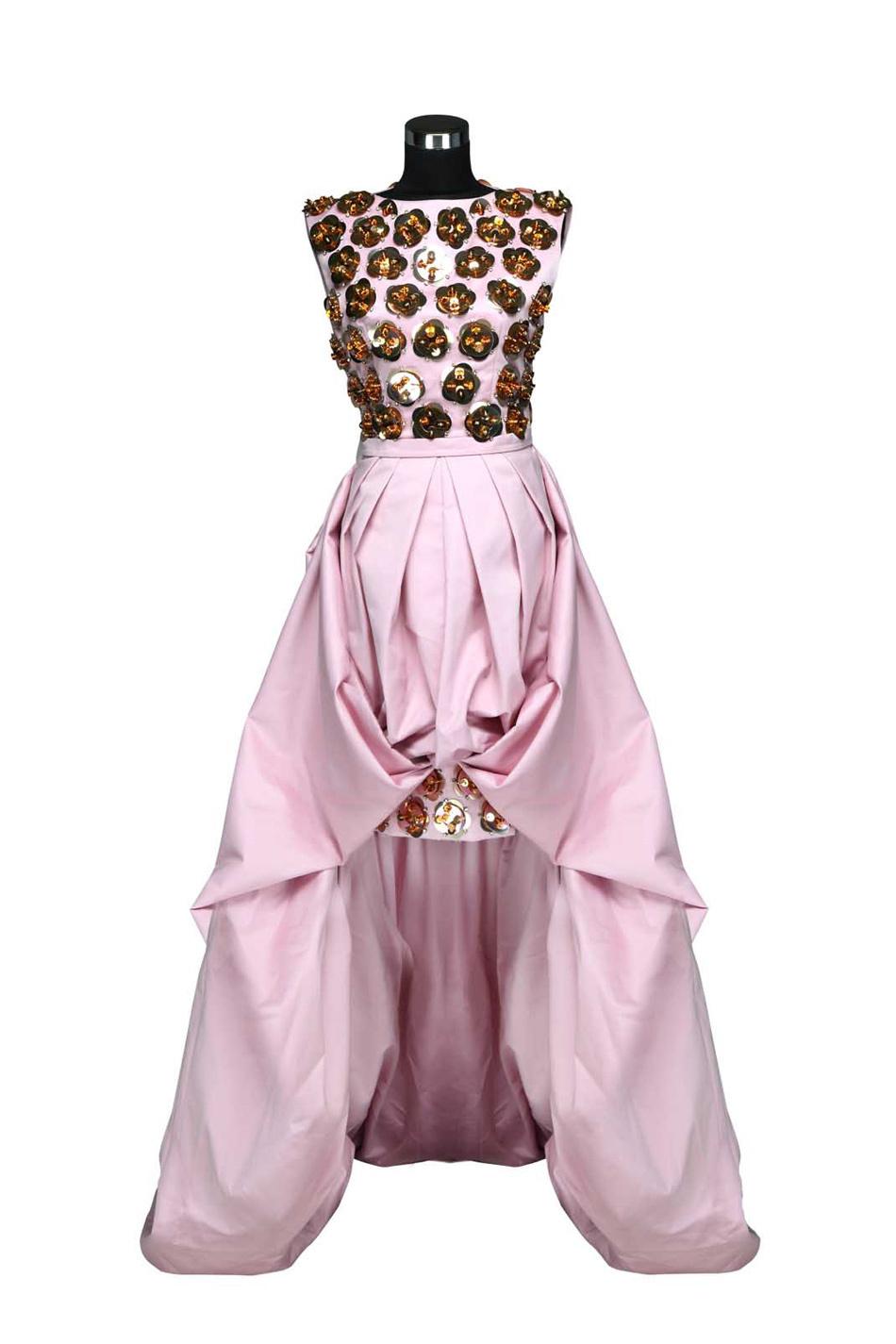 4、Dior 复古华丽粉色晚礼服 Dior的晚礼服以其华美优雅的设计闻名于世,是全球明星名媛的挚爱。 这件复古华丽的粉色晚礼服让人惊艳万分:胸前饰有数朵绽放的立体造型金属花朵,折射出绚烂的光芒;飘逸的裙身设计前短后长、层次丰富;超大的落地式花型裙摆让穿着者摇曳生姿;粉色的绸缎面料柔媚并富于光泽感。这件晚礼服完美融合了奢华风范与上世纪六十年代的摇摆的欢愉与绚烂, 展现出大胆的线条与完美雕刻般的剪裁,是一件瑰丽的设计珍品。 参考价格:RMB 200,000元 Dior pink evening dress