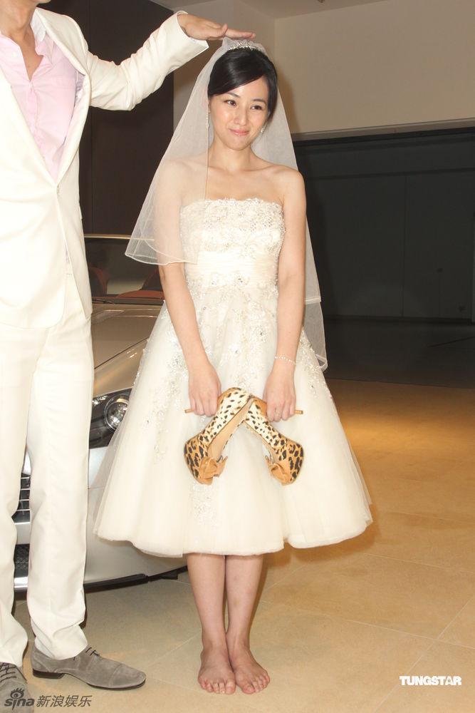 陈怡蓉身着婚纱,与郭品超出席活动.拍照时陈怡蓉脱掉高跟鞋,站在