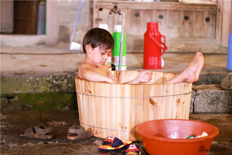 傍晚时在木盆里洗澡的场面更是萌趣十足,诺一康康合力为胖轩穿裤图片