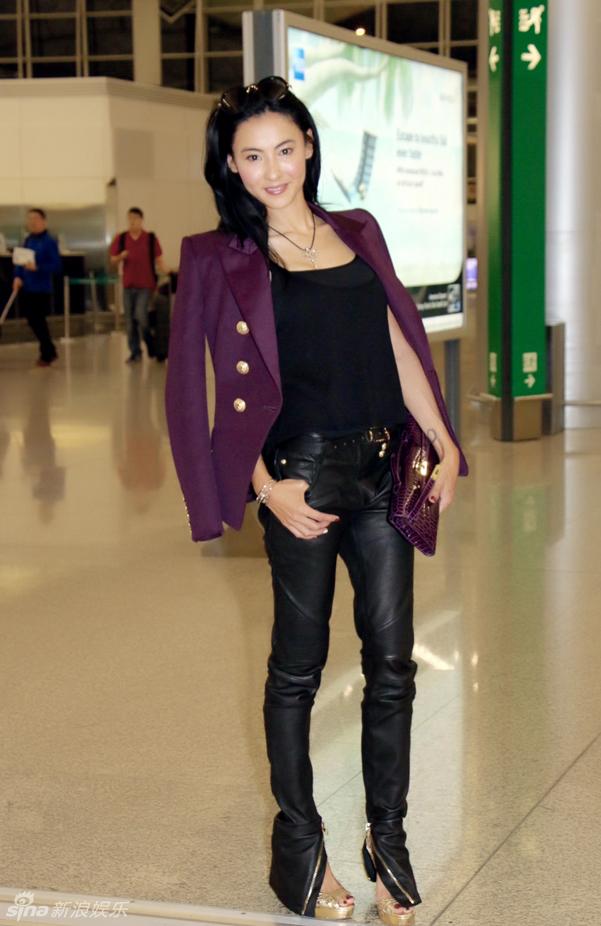 西服,搭配黑色紧身背心和紧身皮裤,将凹凸有致的身材完美展现.-