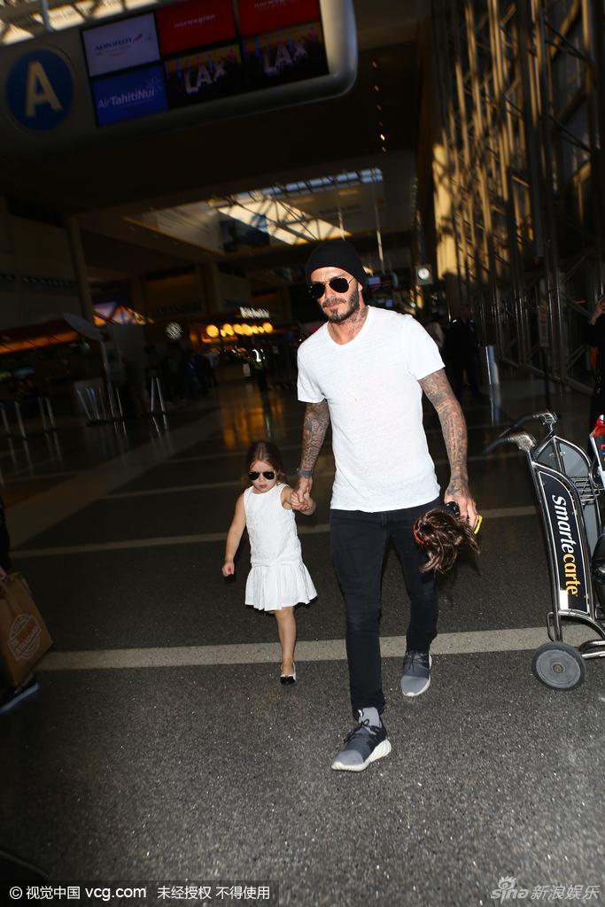 """新浪娱乐讯 当地时间2月20日,贝克汉姆和维多利亚带小七和三个哥哥现身洛杉矶机场。当天,小七与爸爸穿白色""""情侣装"""",一家人颜值爆表!视觉中国/图"""