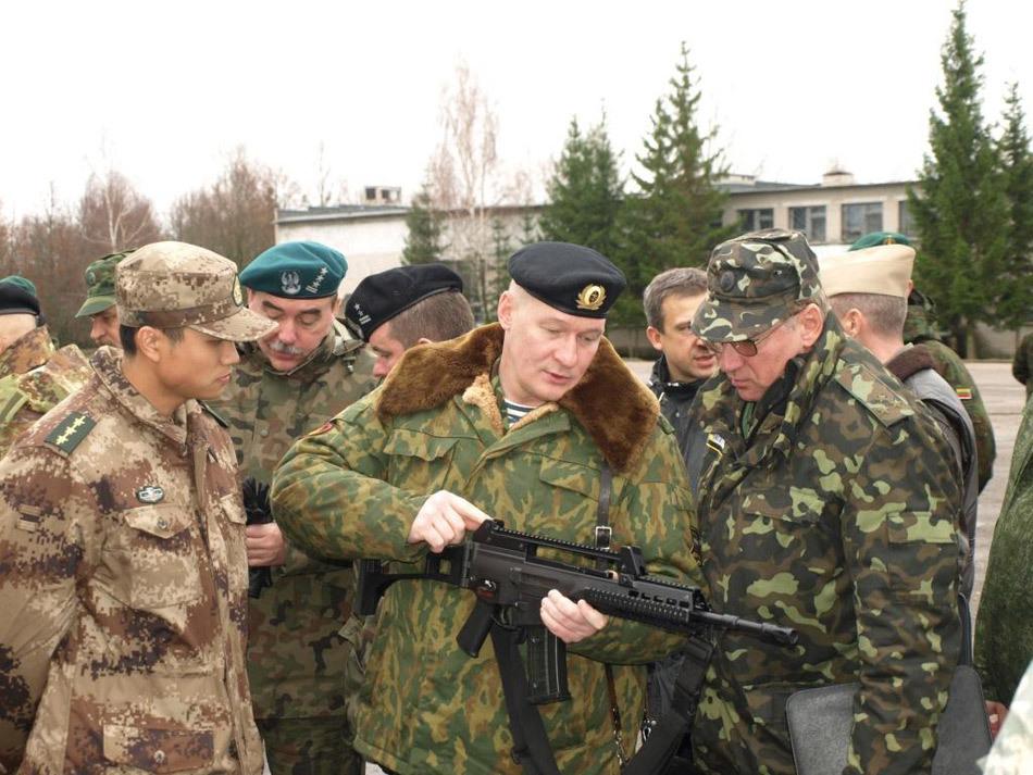 军上尉身着新型07式军服荒漠冬作训服迷彩大衣,在观看外国武官操