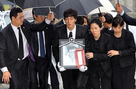 韩星苏志燮(中)手捧朴龙河的遗像走在送殡队伍的最前面(cfp 图)图片