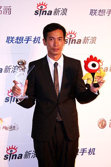 图文:最佳风尚男演员陈豪举起奖杯和小浪人
