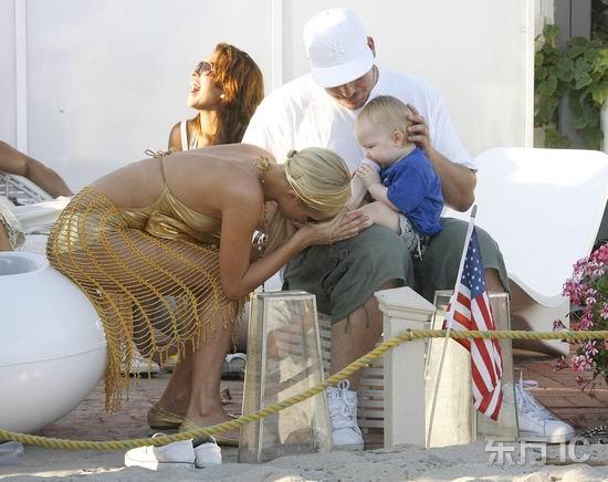 新浪娱乐讯 帕里斯-希尔顿18日一身金光闪闪的泳装腰裹网眼裙在马里布海边大办派对。而她上周末派对的座上客----一个可爱的小男婴这次又被爸爸抱了去凑热闹。   帕里斯前段时间每天都埋在狗堆里,最近却转移了兴趣变得母爱泛滥。只见宝宝刚出现不多久,她就开始慢慢接近目标,先是站着逗了他一会儿,紧接着就在一旁坐了下来。但小可爱只对奶瓶里的东西有兴趣,对眼前的美女却视而不见。不过帕里斯并不气馁,反而加强攻势抓起宝宝一对粉嫩的小脚丫把玩起来,还举到嘴边又嗅又亲。   富家女如此屈尊来讨自己欢心,小宝宝也明显