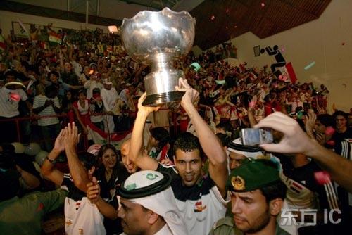 图文-伊拉克队载誉归国尤尼斯高举奖杯走在球迷中