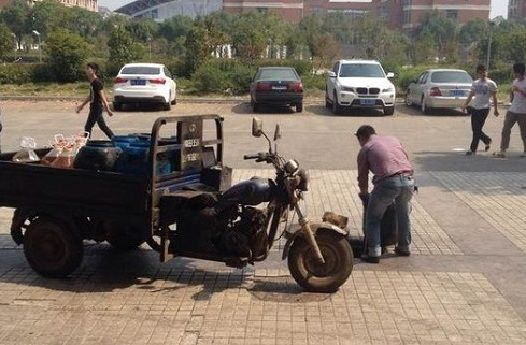 三轮车被撞瞬间遭神秘转移_图片清晰地显示该男子旁边运泔水的三轮车上,不仅装着泔水桶,还装有数