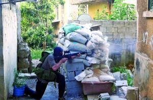 昨日,在黎巴嫩北部城市的黎波里,一名武裝人員持槍做好交火準備。新華/法新